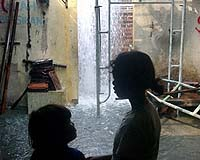 Two girls look at the water gushing from the ground of a restaurant in Jatirejo village near a